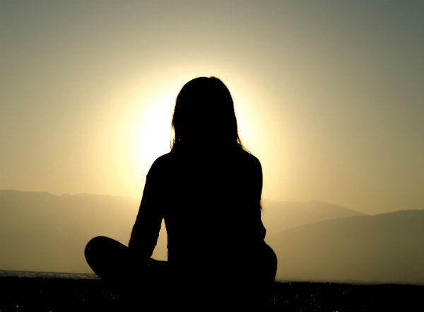 silhouette of lady meditating at sunset